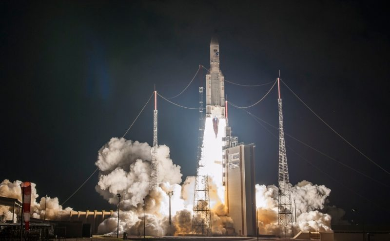 An Ariane 5 rocket launching the JSAT-17 and GEO-KOMPSAT-2B satellites. The rocket's bright plume darkens the sky, while the orange flames shooting out of the white rocket's engines engulf the launch pad.