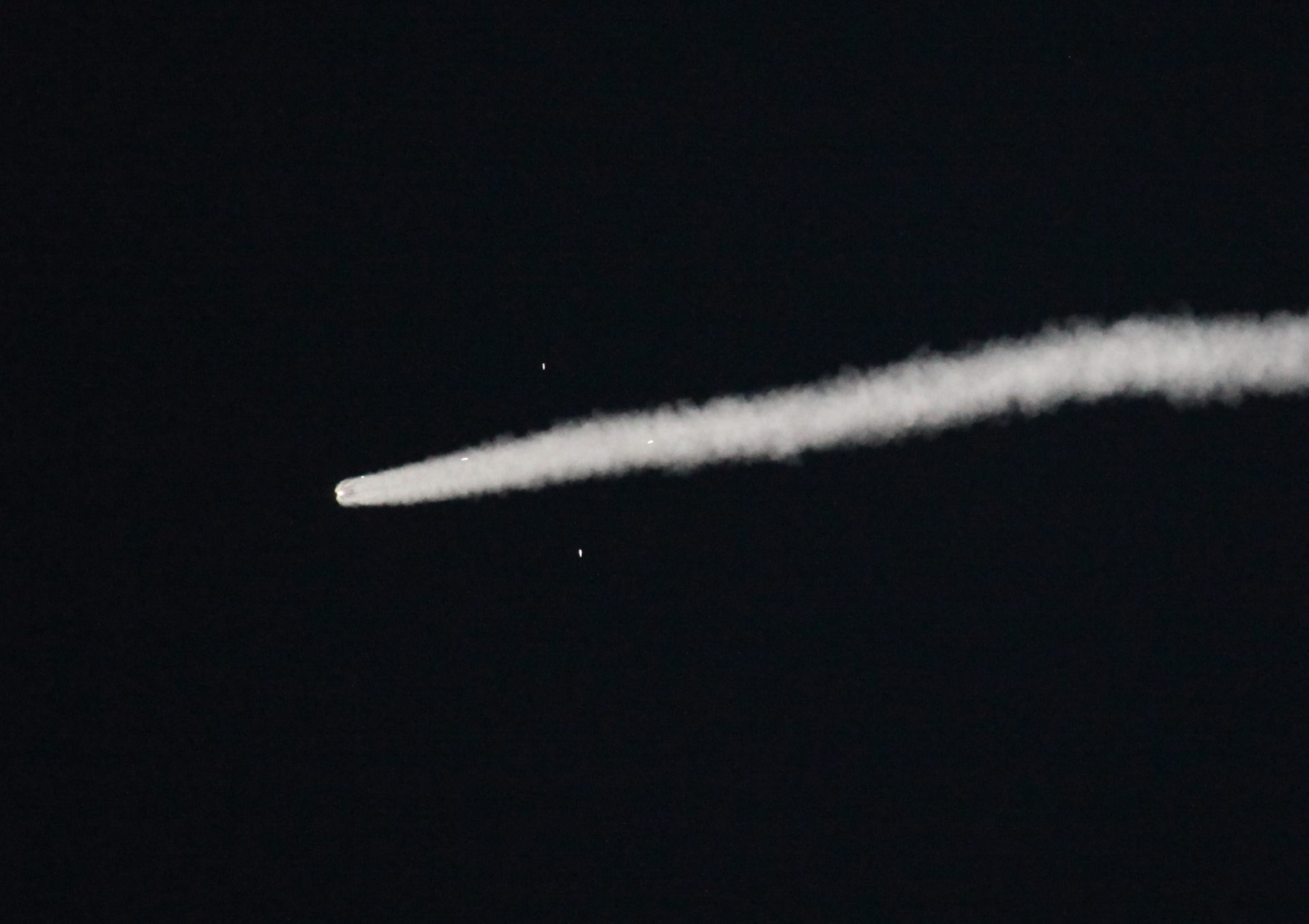 "Rocket in the sky with a white trail of exhaust and four points of light from the boosters engines forming a ""cross"""