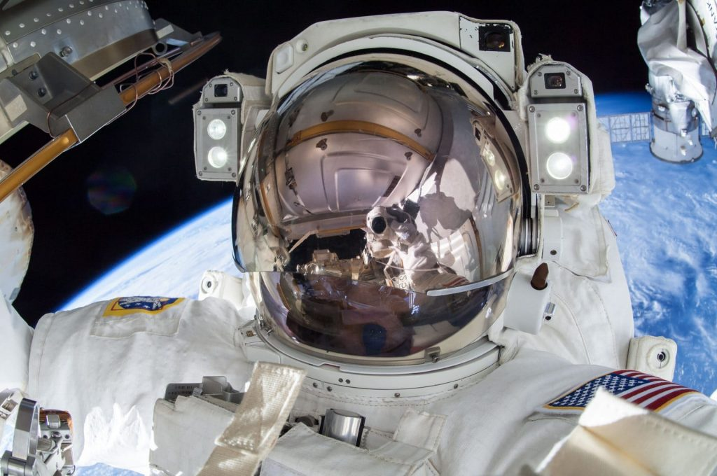 Terry Virts, in white space suit with a blue Earth behind him