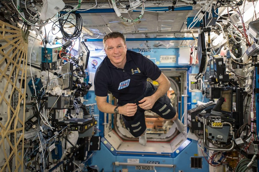 Terry Virts weightless inside the ISS wearing dark pants and a dark short-sleeve shirt. He's seen perfectly centred on all axis.