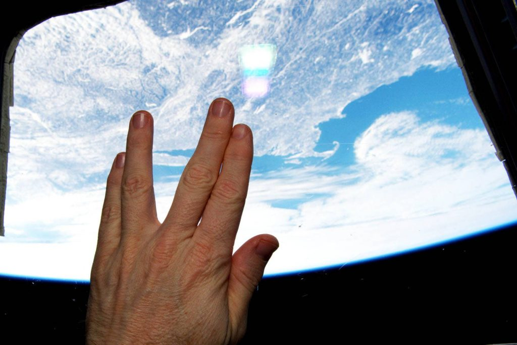 Left hand of Terry Virts spead appart in Vulcan salute with the New England coastline visible as an Earthly backdrop